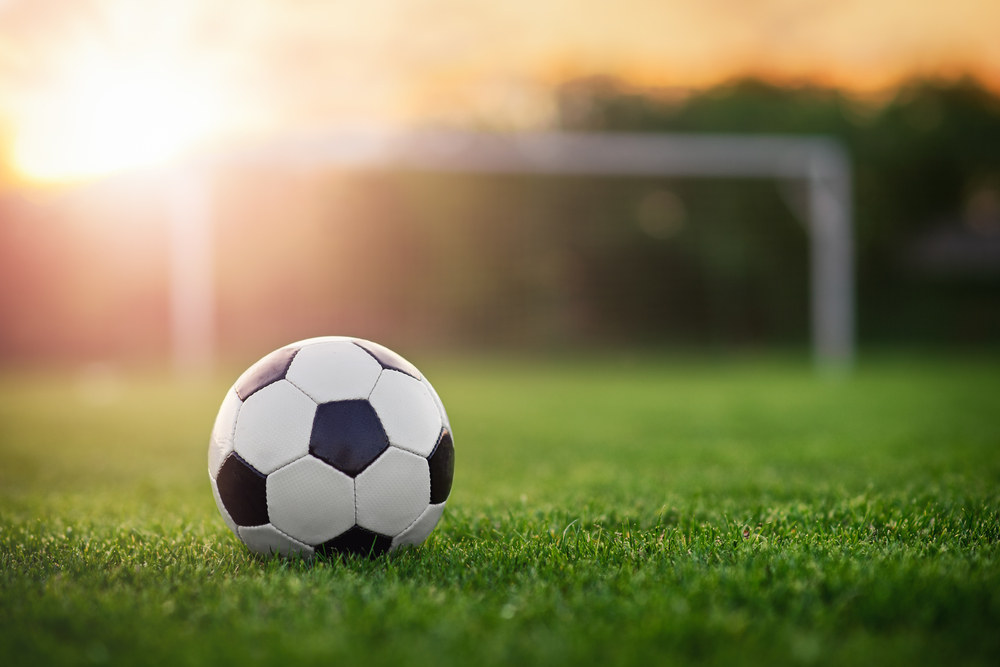 soccer ball on a field at sundown
