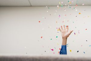 hand throwing confetti in the office