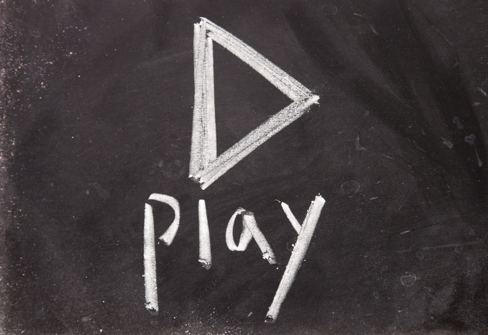 play icon on black chalkboard